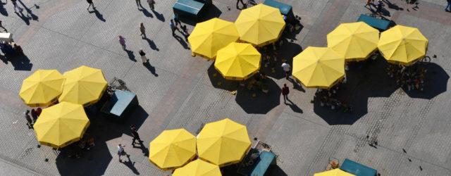 Die typisch gelben Schirme auf dem Hauptplatz Rynek Glowny von Krakau